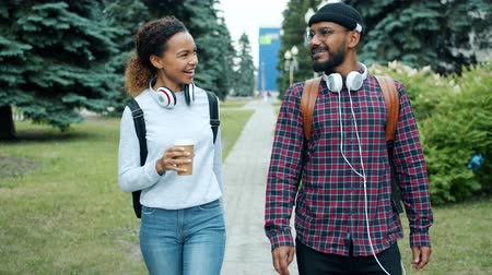 go to school : Couple of students walking outdoors on campus chatting drinking coffee enjoying warm autumn day and funny conversation. People and lifestyle concept.