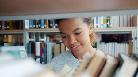 bookshop : Beautiful African American teenage girl choosing books in college library reading smiling enjoying modern literature. People, culture and education concept. Stock Footage