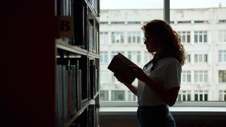 knihkupectví : Slow motion of smiling student choosing book in school library reading standing near bookshelf alone holding volume. Literature and education concept.