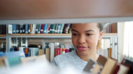 книжный шкаф : Close-up slow motion of pretty mixed race woman looking through books in library smiling choosing literature for education. Youth and reading concept.