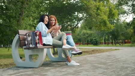 multi media : Beautiful girls teenagers are using smartphones relaxing on bench in park laughing chatting having fun together, shopping bags are visible. People and lifestyle concept.