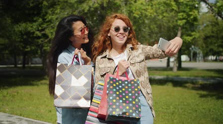 multi media : Pretty girls friends are taking selfie with smartphone camera holding shopping bags in city park posing having fun. People, devices and consumerism concept.
