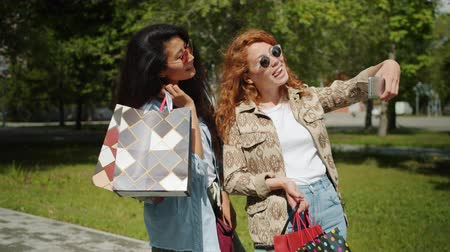 multi media : Couple of girls taking selfie with smartphone camera holding shopping bags in park posing having fun expressing positive emotions. People and gadgets concept.