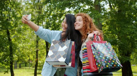 multi media : Slow motion of Asian lady taking selfie with Caucasian friend outdoors after shopping day walking in park using modern device. Lifestyle and photo concept.
