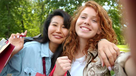рыжеволосый : Attractive ladies friends are taking selfie in park with shopping bags looking at camera smiling posing with happy faces. Friendship and lifestyle concept.