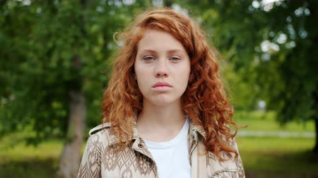 dospívání : Serious teenager beautiful redhead girl is looking at camera standing outdoors in park wearing casual clothing. People, nature and emotions concept. Dostupné videozáznamy