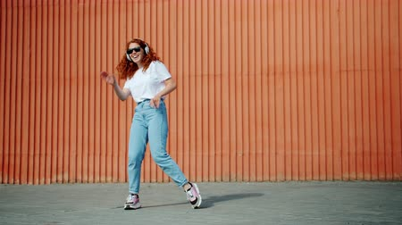 buta : Joyful young lady carefree student is dancing outdoors wearing headphones and sunglasses having fun outside alone. Lifestyle and active youth concept.