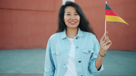 foreigner : Slow motion portrait of cheerful Asian woman holding official German flag and looking at camera standing outdoors alone. Travelling and youth concept.