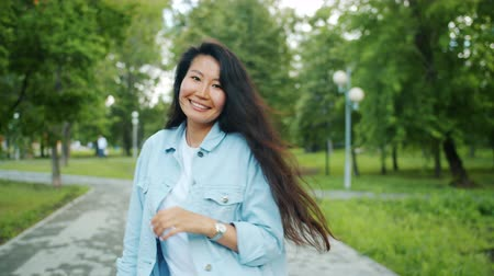 fejlövés : Slow motion of happy Asian woman walking in green park alone then turning to camera showing thumbs-up smiling laughing. People and happiness concept. Stock mozgókép