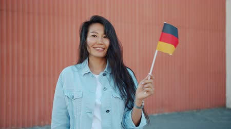 иностранец : Happy Asian girl student is waving German flag standing outdoors smiling looking at camera alone. European countries, travelling and patriotism concept. Стоковые видеозаписи