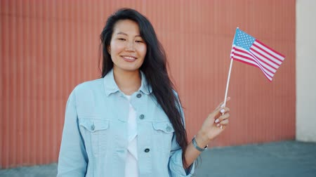 büszke : Portrait of pretty Asian girl holding official US flag outdoors smiling looking at camera expressing patriotic feelings. People, countries and tourism concept. Stock mozgókép