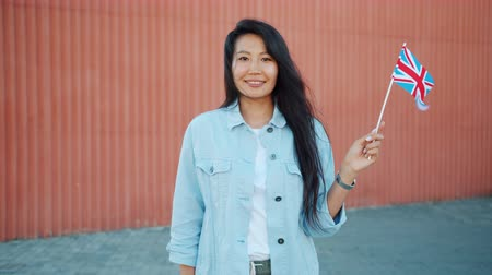 nationality : Slow motion of cute Asian lady holding British flag smiling looking at camera standing alone outdoors against wall. Youth, travelling and lifestyle concept. Stock Footage