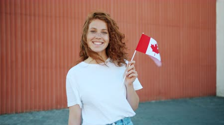 drapeau canadien : Slow motion of happy female student beautiful redhead lady holding Canadian flag outdoors smiling looking at camera. Tourism, patriotism and youth concept. Vidéos Libres De Droits
