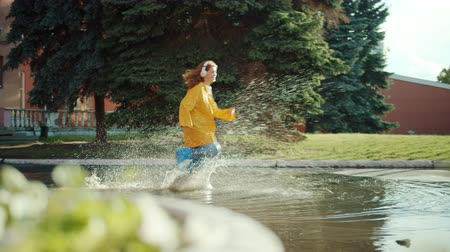 regenjas : Girl in bright raincoat and gumboots is running in puddles wearing headphones having fun splashing in water. Lifestyle, leisure and devices concept.