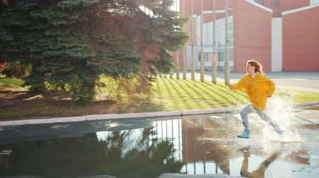 gumboots : Slow motion of joyful girl in bright raincoat and rubber boots running in puddles outdoors having fun alone. Happiness, weather and lifestyle concept. Stock Footage