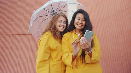 multi media : Cheerful young women in raincoats are using smartphone outdoors under umbrella touching screen swiping smiling. Modern technology and autumn concept.