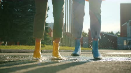 gumboots : Close-up slow motion of female legs in colorful rubber boots jumping in puddle outdoors having fun on sunny autumn day. Lifestyle and weather concept.