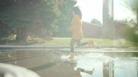 gumboots : Slow motion of pretty Asian girl in bright raincoat and gumboots running in puddles in city park on autumn day. Weather, nature and lifestyle concept. Stock Footage