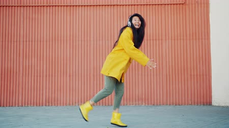 gumboots : Cheerful Asian lady in yellow raincoat and rubber boots dancing outdoors having fun wearing headphones listening to music. People, clothes and lifestyle concept.