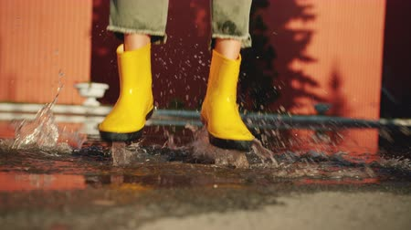 gumboots : Close-up of female feet in bright rubber boots jumping in puddle outdoors on sunny day enjoying funny activity. Happiness, people and weather concept. Stock Footage