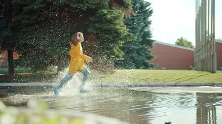 gumboots : Happy teenager in colorful raincoat and gumboots running in puddles wearing headphones enjoying leisure time activity. Happiness, youth and music concept.