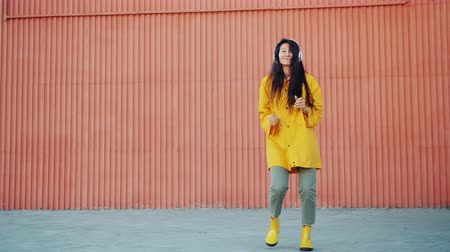 gumboots : Slow motion of pretty young Asian girl dancing outdoors wearing raincoat and gumboots enjoying song in headphones. People, autumn and happiness concept.