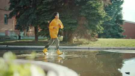 raincoat : Beautiful Asian woman student is running in puddles wearing wet clothing raincoat and gumboots enjoying joyful activity. Youth, weather and people concept. Stock Footage