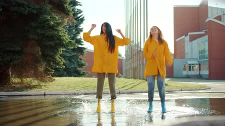 impermeabile : Slow motion of happy friends beautiful young women jumping in puddle wearing rubber boots and raincoats having fun together. Friendship and autumn concept.