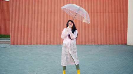 gumboots : Slow motion of beautiful Asian woman in raincoat and rubber boots dancing outdoor with umbrella having fun alone. People, autumn and lifestyle concept.