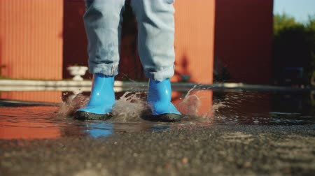 gumboots : Slow motion of feet in bright blue gumboots jumping in pool having fun on autumn day enjoying outdoor activity. Lifestyle, entertainment and footwear concept. Stock Footage