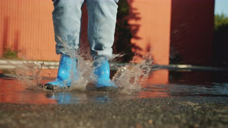 gumboots : Female legs in colorful gumboots are jumping in puddle on the ground enjoying autumn having fun. Happiness, outdoor activity and joyful people concept.
