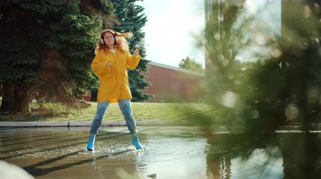 regenjas : Student attractive redhead girl in raincoat and gumboots is jumping in puddle listening to music in headphones having fun. Lifestyle and emotions concept.
