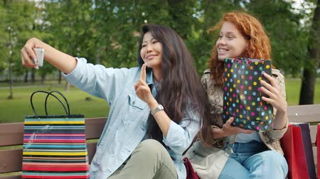 multi media : Cheerful girls friends are taking selfie with shopping bags sitting on bench in park posing smiling. Consumerism, photograph and modern technology concept.