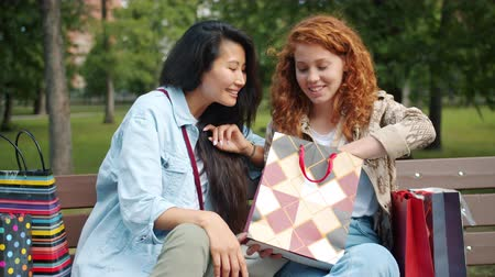 подростковый возраст : Slow motion of cheerful ladies friends looking at purchases in shopping bags on bench in park chatting laughing. Lifestyle, consumerism and people concept.
