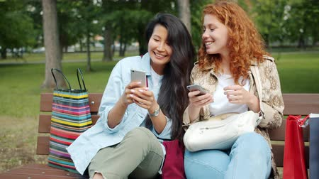 multi media : Cheerful girls friends are using smartphones chatting relaxing on bench in park together with shopping bags. Modern technology, lifestyle and people concept.