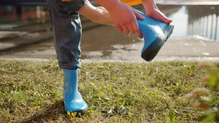 gumboots : Close-up of female hand taking off rubber boot from bare foot and pouring out water on autumn day, puddle is visible in background. People and weather concept.