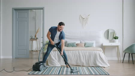 housekeeper : Slow motion of happy middle-aged guy cleaning home with vacuum cleaner and dancing having fun enjoying housework. People, lifestyle and devices concept.