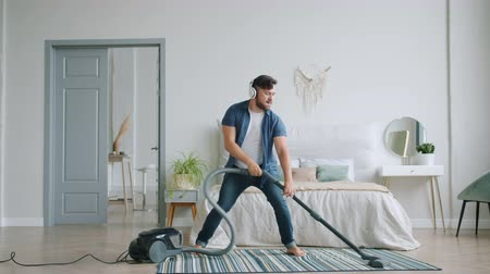 arrumado : Slow motion of funny guy vacuuming floor at home with vacuum cleaner having fun dancing in modern apartment. People, lifestyle and gadgets concept. Vídeos