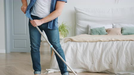mopping : Tilt-down of handsome middle-aged guy washing laminate floor with mop barefoot doing housework in apartment. Household, people and manual work concept.