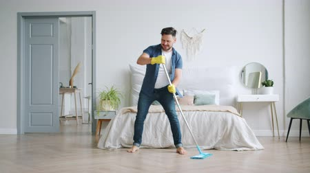 laminát : Smiling brunet in rubber gloves is washing wooden floor with plastic mop and dancing at home enjoying household activities. People and apartment concept. Dostupné videozáznamy