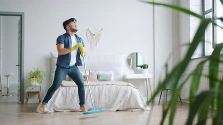 mopping : Cheerful young man is dancing singing washing floor in apartment with plastic mop having fun listening to music. Entertainment and lifestyle concept.