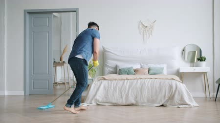 mopping : Slow motion of attractive young man in rubber gloves washing wooden floor and dancing with plastic mop having fun in flat. People and housework concept.