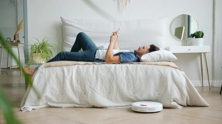 청소기 : Guy is sufring the Internet with smartphone relaxing in bed while robotic vacuum cleaner is cleaning floor removing dust from laminate. Gadgets, people and housekeeping concept.