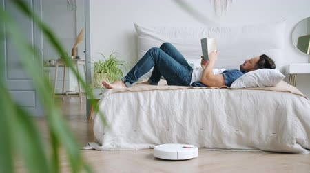 čtenář : Carefree man is reading book in bed while robotic vacuum cleaner is vacuuming floor in bedroom caring for hygiene in apartment. People and devices concept.
