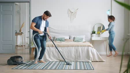 housekeeper : Man and woman happy couple are having fun during clean-up at home vacuuming and dusting enjoying music dancing. Housekeeping, people and happiness concept.