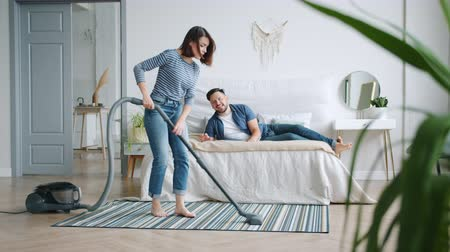 уборка : Slow motion of happy girl vacuuming floor in bedroom while guy husband lying in bed having fun on clean-up day. People, housework and relationship concept.