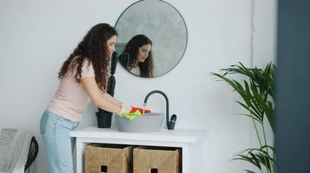 моющее средство : Pretty young lady housekeeper is washing bathroom sink with wet cloth wearing rubber gloves and casual clothing. People, housework and lifestyle concept. Стоковые видеозаписи