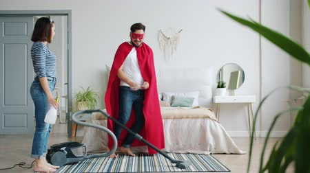 герои : superhero is dancing with vacuum cleaner then running away when woman is coming home with bottle sprayer. Lifestyle, housework and fun concept.