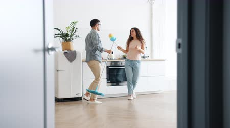 швабра : Happy young couple dancing in kitchen holding mop and duster having fun on clean-up day in studio apartment. Modern youth, people and housekeeping concept. Стоковые видеозаписи