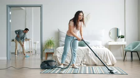 appareil menager : Girl and guy cleaning floor at home using vacuum cleaner and mop doing housework together during clean-up day. People, family lifestyle and youth concept.